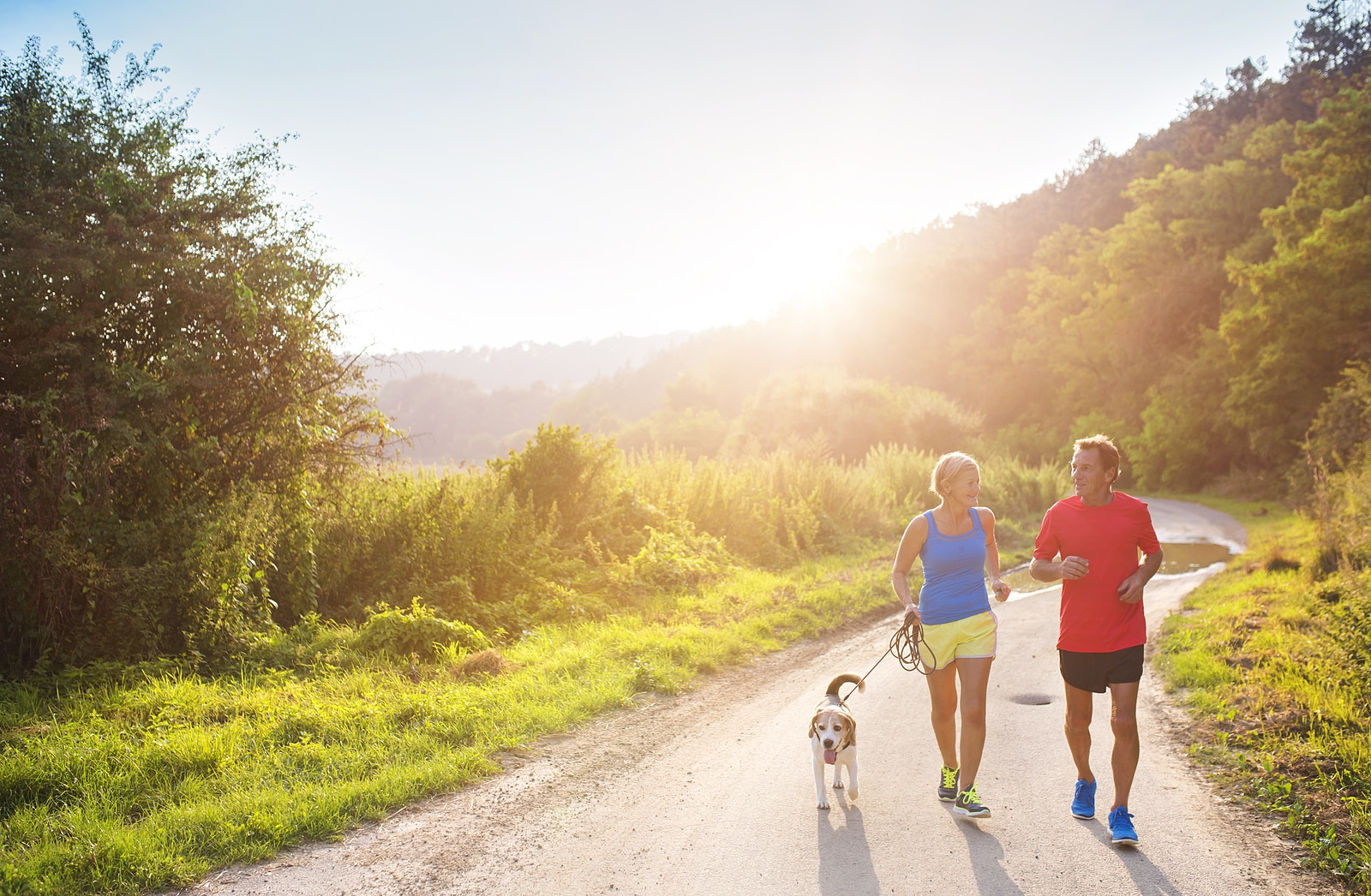 Couple in running gear run on a mountain trail with a beagle leashed beside them.