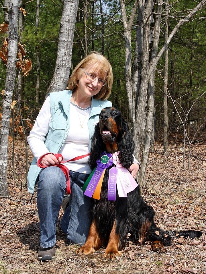 Susan with a brown and black curly haired spaniel with ribbons around the neck.